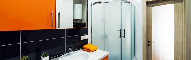 Pomarańczowe meble łazienkowe i czarne płytki ceramiczne – projekt nowoczesnej łazienki
